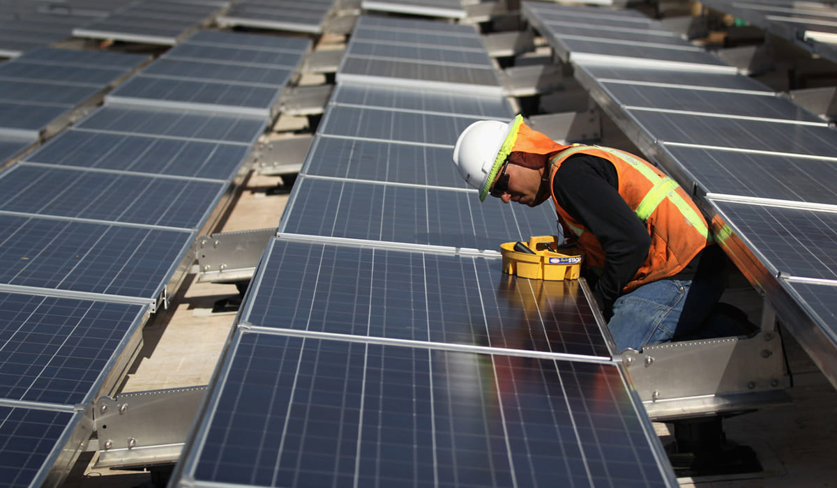 A worker installs solar panels atop a government building in Lakewood, Colo. The industry has added more than 80,000 jobs since 2010, according to The Solar Foundation.